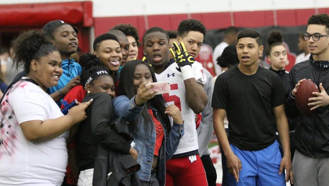 Badgers cornerback Derrick Tindal helps entertain students from McFarland High School in Madison during a field trip to recent visit the UW football team.