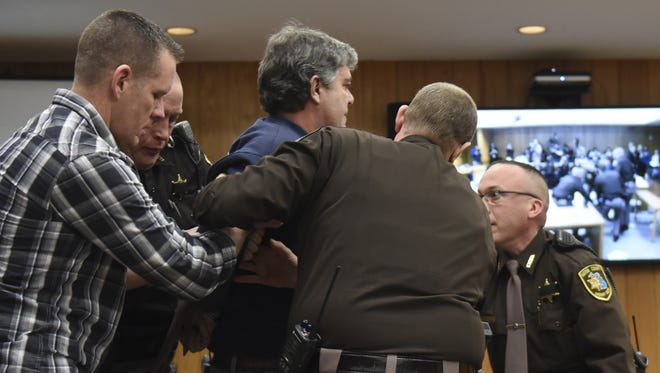 Randall Margraves, father of Lauren, Madison and Morgan Margraves, is detained after trying to attack Larry Nassar, Friday, Feb. 2, 2018, in Eaton County Circuit Court during the second day of victim impact statements in Judge Janice Cunningham's courtroom in Charlotte, Mich.