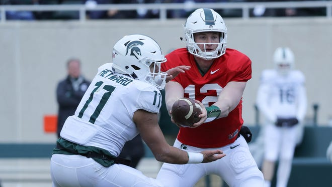 Michigan State quarterback Rocky Lombardi hands off to running back Connor Heyward during the annual spring game Saturday, April 7, 2018 at Spartan Stadium.