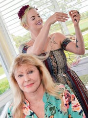 Pat Bechtel gets fairy hair from Sara Shadel of Glittering Gypsies at the St. Lucie West Garden Club's annual luncheon and fashion show at The Legacy in Port St. Lucie's PGA Village.