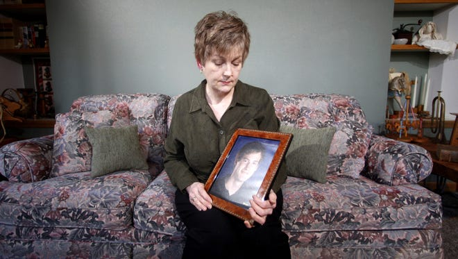 FILE ? In this Monday, Feb. 27, 2012 file photo, Karen Williams, who sued Facebook for access to her 22-year-old son Loren?s account after he died in a 2005 motorcycle accident, looks at a portrait of her son at her home in Beaverton, Ore. The Uniform Law Commission on Wednesday, July 16, 2014 was expected to endorse a plan to automatically give loved ones access to ? but not control of ? all digital accounts, unless otherwise specified.  (AP Photo/Rick Bowmer, File)