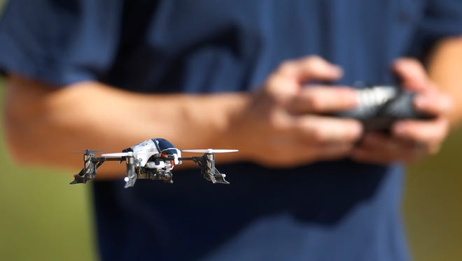 Jim Allen flies his Heli-Max 1SQ Quadcopter Sunday, Aug. 17,  2014 in Mesa, Ariz.  A proposed Phoenix ordinance would make it a crime to use a drone to film or photograph people on their private property without their knowledge, a law which Jim supports.