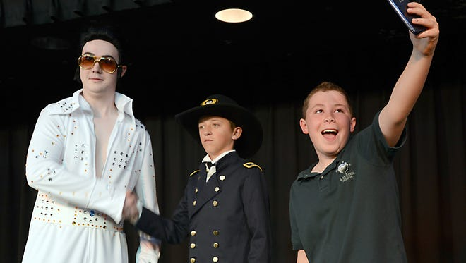 """Small Child 2014 (Matt Hutchinson) takes a """"selfie"""" with Elvis (David Newman) and Gen. Ulysses Grant (Noah Columbo) during a rehearsal of the play, """"Nevada: It's Not Just Vegas, Baby."""""""