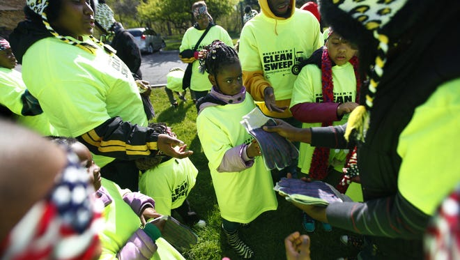 Sanaria Robinson, center, and Eursla McNair, left, both of Rochester, receive gloves to pick up trash at Maplewood Park during the city's first Clean Sweep in 2012.