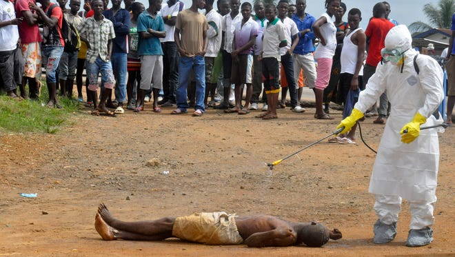 A health worker sprays a man suspected of dying from Ebola with disinfectant in Monrovia, Liberia, on Sept. 4.