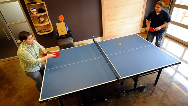 Keith Cawley and Stephen Belcher of Technology Advice play a match of ping-pong March 12, 2014. The company is assessing how  the way someone plays ping-pong correlates to their success in the workplace.