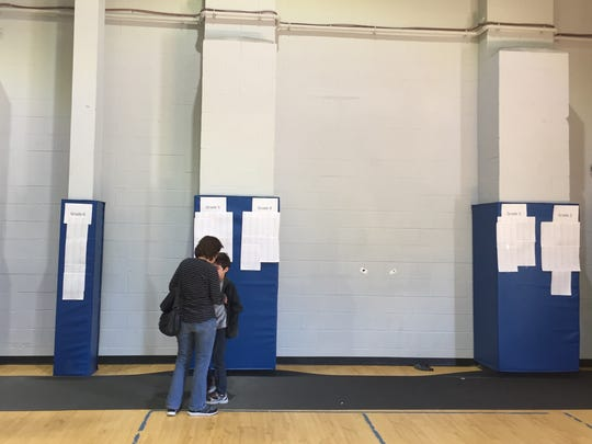Two people looking at the waiting list for enrollment
