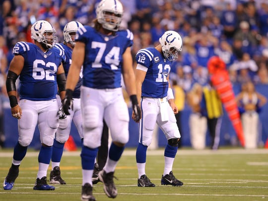 Indianapolis Colts quarterback Andrew Luck (12), right, and the rest of the offense walk off the field after turning the ball over to New England after a failed fourth-down attempt during second half action of an NFL football game Sunday, Oct. 18, 2015, at Lucas Oil Stadium.