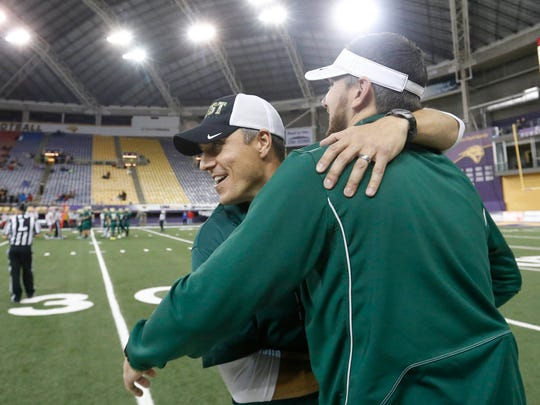 Iowa City West head coach Garrett Hartwig celebrates with his coaching staff as his team gets the win over Cedar Rapids Washington Friday, Nov. 11, 2016, during their 4A state semifinal game at the UNI Dome in Cedar Falls.