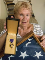 Janet Bodner holds her husband's Purple Heart and the