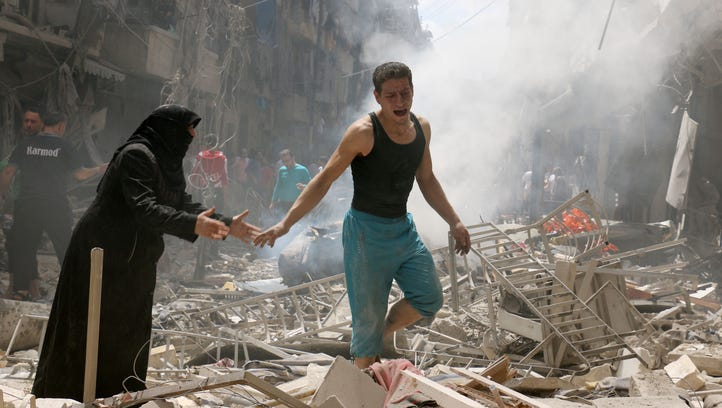 People walk amid the rubble of destroyed buildings