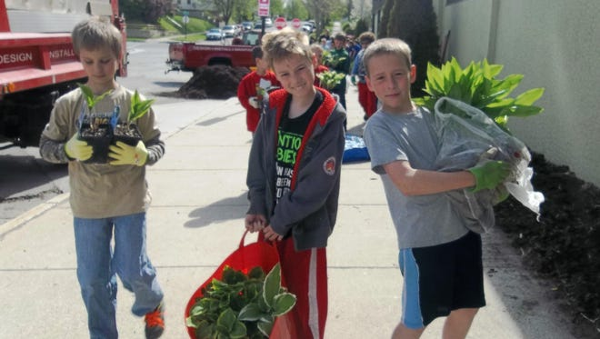 "This spring, Sheboygan Leadership Academy's fourth-grade class was involved in a S.T.E.M. project called ""Making a Process: Planting and Caring for a Garden."" From left, fourth-graders Evan Behnke, Casey Hanson and Victor Spaeth transport plants."