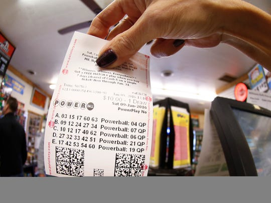 In this photo made with a fisheye lens a clerk hands a patron his $10 worth of chances for the upcoming Powerball drawing on Saturday, in Cranberry Township, Pa. The Powerball jackpot has reached a record $900 million, with the drawing Saturday night.