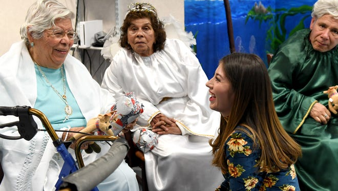 Flor Chavarin and Elvira Cabello chat with assistant social worker Elizabeth Campos during the Christmas Eve Posada at the La Casa Adult Day Health Center on Friday.