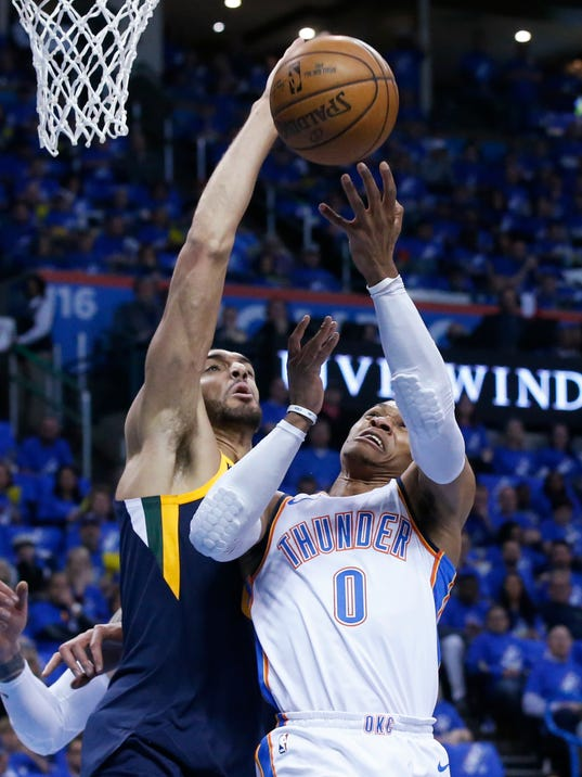 Utah Jazz center Rudy Gobert, left, blocks a shot by Oklahoma City Thunder guard Russell Westbrook (0) in the first half of Game 1 of an NBA basketball first-round playoff series in Oklahoma City, Sunday, April 15, 2018. (AP Photo/Sue Ogrocki)