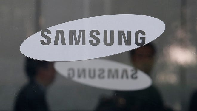 In this Oct. 31, 2017, file photo, employees walk past logos of the Samsung Electronics Co. at its office in Seoul, South Korea.
