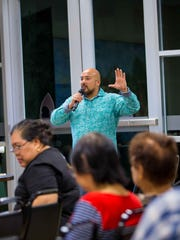 Filipino Community of Guam President Norman Analista gestures for FCG members to show support for the upcoming raffle of the 2017 Honda Accord donated by Triple J Honda.