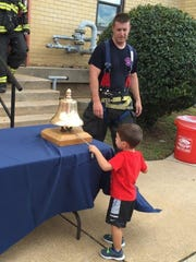 Mikey Brago, 2, rings the fire bell after accompanying