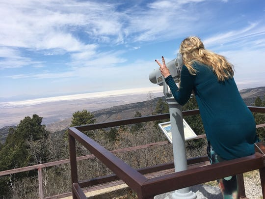 A hiker looked at the Tularosa Basin scenery through binoculars from Sunspot Observatory in 2018.