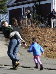 A mother runs with her children as police above canvass