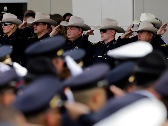 Officers salute during services for San Antonio police officer Miguel Moreno, Friday, July 7, 2017, in San Antonio. Moreno died of wounds suffered when he and his partner were shot by a man they intended to question about a vehicle break-in last week. (AP Photo/Eric Gay)