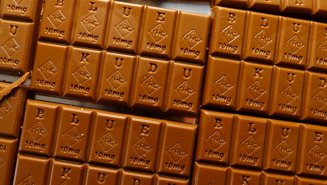 In this Monday, Sept. 19, 2016, photograph, candy bars marked with Colorado's new required diamond-shaped stamp noting that the product contains marijuana are shown in the kitchen of BlueKudu candy in the historic Five Points District of Denver. State officials require the stamp to be put directly on edibles after complaints that the treats look too much like their non-intoxicating counterparts. (AP Photo/David Zalubowski)