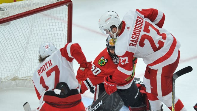 Red Wings rookie Michael Rasmussen scores his first NHL goal against Blackhawks goalie Corey Crawford, as teammate David Booth looks on in the second period of an exhibition game Thursday, Sept. 21, 2017 in Chicago.