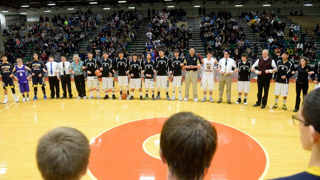 Four teams -- Heart Butte, Box Elder, Belt and Power -- interlock arms at center court at the Northern C Divisional basketball tournament in 2016 in a show of solidarity.