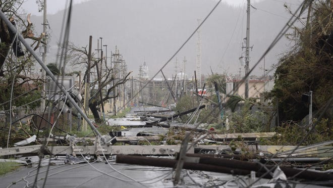 Electricity poles and lines lay toppled on the road after Hurricane Maria hit the eastern region of the island, in Humacao, Puerto Rico, Wednesday, Sept. 20, 2017. The strongest hurricane to hit Puerto Rico in more than 80 years destroyed hundreds of homes, knocked out power across the entire island and turned some streets into raging rivers in an onslaught that could plunge the U.S. territory deeper into financial crisis. (AP Photo/Carlos Giusti)