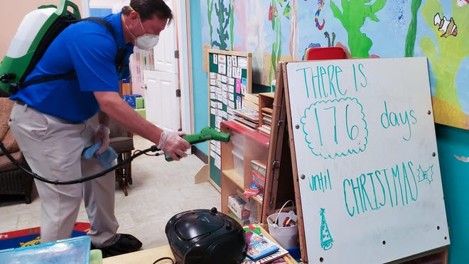 Zack Greer, owner of Ecovasive North Florida Infection Control, decontaminates a preschool in Nocatee Thursday afternoon.