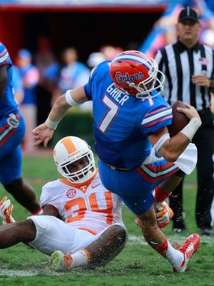 Tennessee Volunteers linebacker Darrin Kirkland Jr. (34) tackles Florida Gators quarterback Will Grier (7) during the first half at Ben Hill Griffin Stadium.