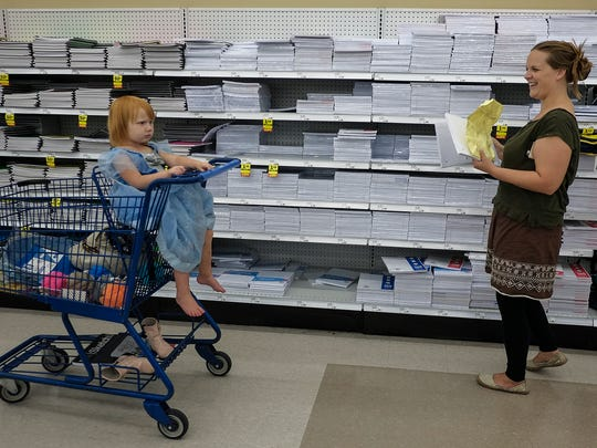 """East Lansing resident Maryellen Sandford laughs at the antics of her two-year-old daughter Gambrelle while shopping at the Lake Lansing Road Meijer for school supplies for her four sons Monday, August 29, 2016. Working from a printed list she said """"It's not the first time I have been here."""""""