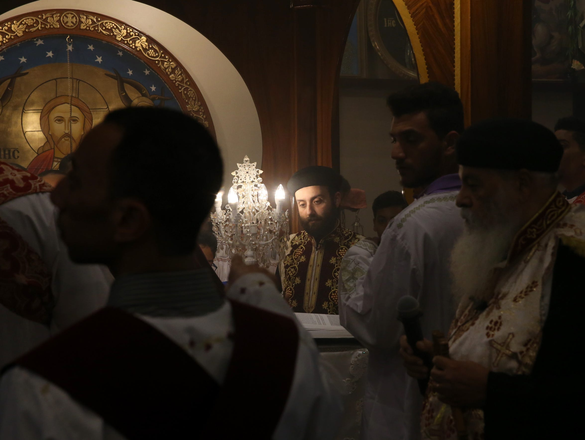 Father Jerome, center, performs a ceremony surrounded by deacons at the St. Mary & St. George Coptic Orthodox Church as they observe Good Friday at their church on April 14, 2017.