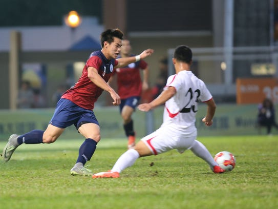 Guam's Edward Na manages to get the ball around a DPR