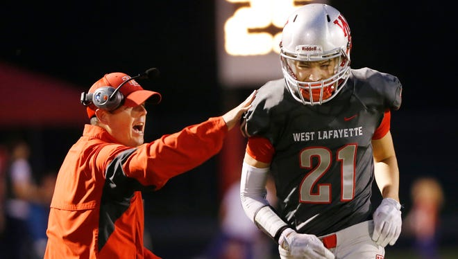 Harrison Truitt gets a pat on the back from West Lafayette head coach Shane Fry after his touchdown reception at 8:58 in the first quarter put the Red Devils up 7-0 over Twin Lakes Friday, October 6, 2017, at Gordon Straley Field in West Lafayette. West Lafayette pounded Twin Lakes 70-0.