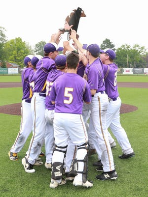 Plymouth Christian Academy baseball players lift their first-ever Division 4 regional championship trophy.