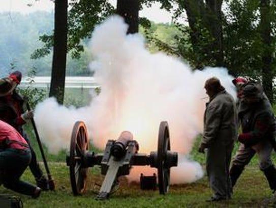 Confederate Civil War re-enactors fire a cannon as