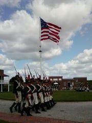 Reenactors march below the 15-star American flag at