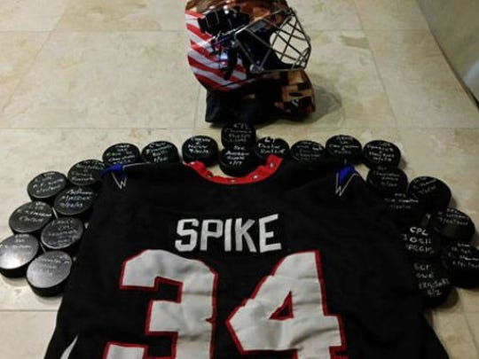 "Keith ""Spike"" Schneider puts the names of fallen soldiers"