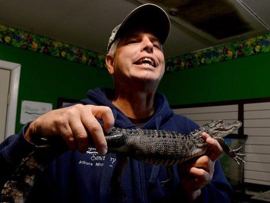 David Critchlow holds an alligator named Alphabet Soup,