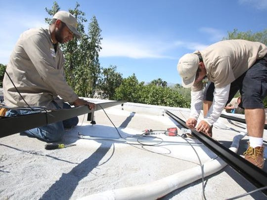 HelioPower employees Tim Vela and Henry Sandoval prepare