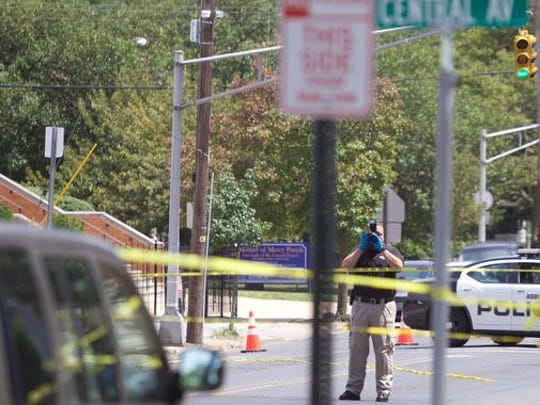 Police take photos following a double shooting on First Avenue in Asbury Park on Aug. 6.