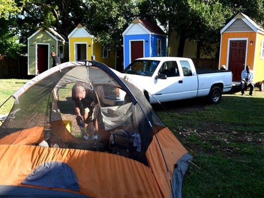 Roger McGue helps take down a friend's tent at a homeless