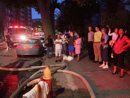 Residents watch as firefighters work at a three-alarm fire at 200 Valentine Lane in Yonkers early Friday.