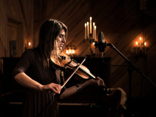 Lizzy Plotkin plays the fiddle during a music benefit