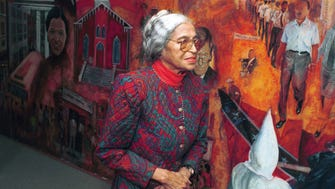 Rosa Parks walks by the civil rights mural at Dexter Avenue King Memorial Baptist Church on Nov. 21, 1991. She was at the church for a Montgomery Improvement Association meeting.