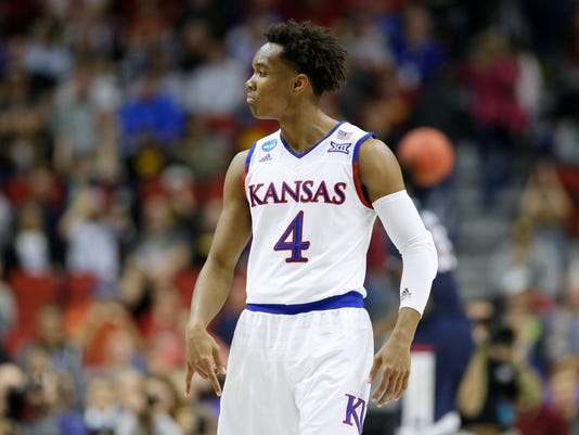 Kansas guard Devonte' Graham celebrates after making a 3-point basket during the second half of a second-round men's college basketball game against Connecticut in the NCAA Tournament, Saturday, March 19, 2016, in Des Moines, Iowa. Kansas won 73-61.(AP Photo/Charlie Neibergall)