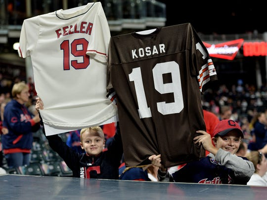 Two Cleveland Indians fans hold up jerseys of former Indians player Bob Feller and Browns player Bernie Kosar to signify the Indians 19th win in a row after the Tigers' 11-0 loss to the Indians on Monday, Sept. 11, 2017, in Cleveland.