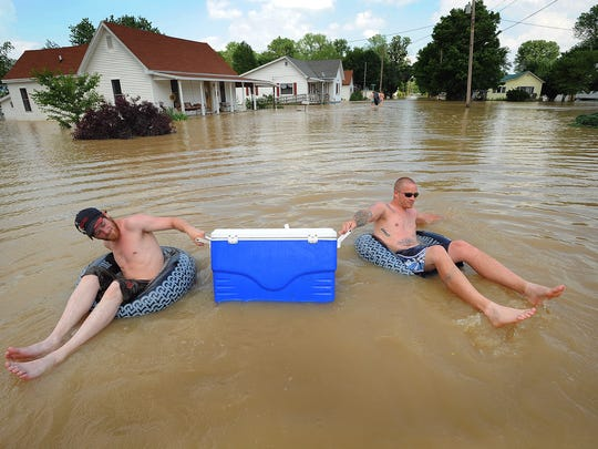 Ryan Lewis,left, and Joe Conway,right, flood down 3rd Street to thier house keeping their beverages high and on ice Monday afternoon in Worthington IN. (Matt Kryger / The Indianapolis Star)