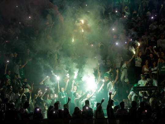 Supporters of the Chapecoense soccer team light flares inside Arena Condado stadium in Chapeco, Brazil, Wednesday, Nov. 30, 2016, as they pay tribute to members of their team who died in an airplane crash in Colombian on Monday night. (AP Photo/Andre Penner)